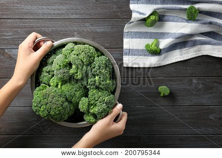 Hands holding colander with fresh green broccoli with brown wooden table on background