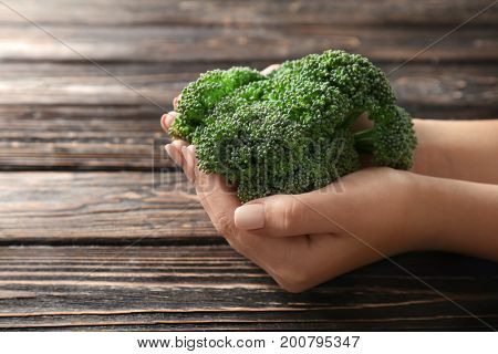 Fresh green broccoli in hands with background of wooden table