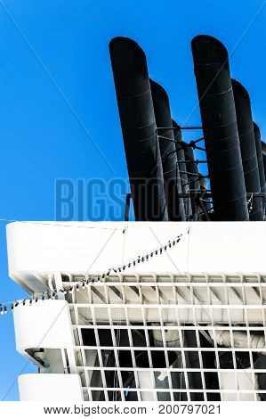 Cut detail of a ship chimney in white and black against a blue sky high contrast