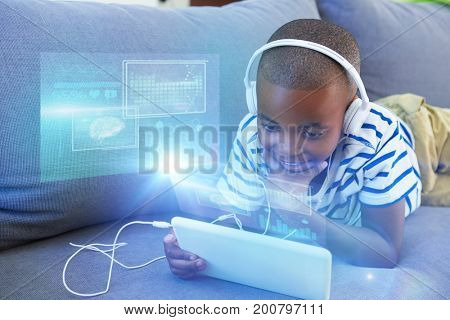 Digital image of brain with DNA helix and graph against boy using digital tablet while listening to headphones on sofa at home