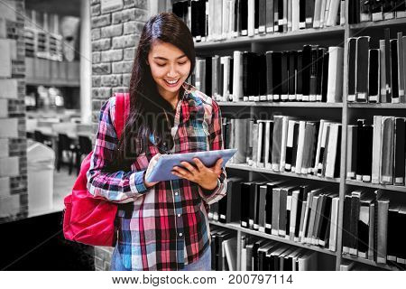 Smiling student using tablet in library at university