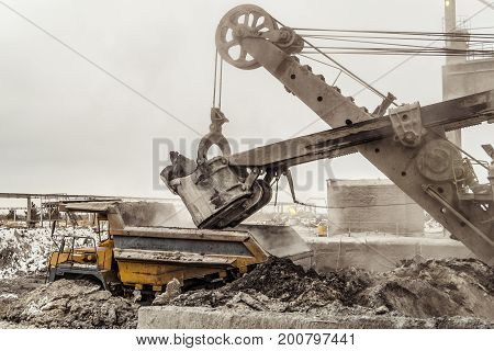 Bucket excavator loads into a large mining dump truck. Heavy industry.