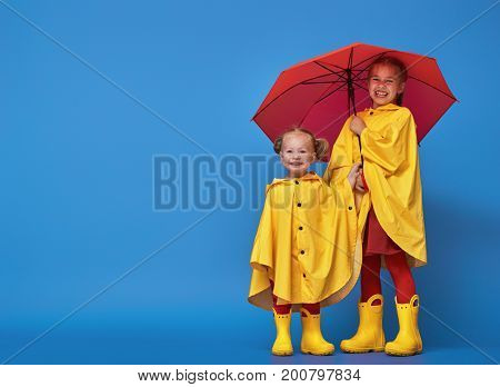Two happy funny children with red umbrella posing on blue wall background. Girls is wearing yellow raincoat and rubber boots.