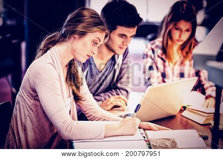 Focused classmates studying together while using laptop in library