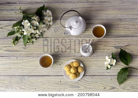 Cups with jasmine tea, a bouquet of jasmine and shortbread on a wooden table closeup