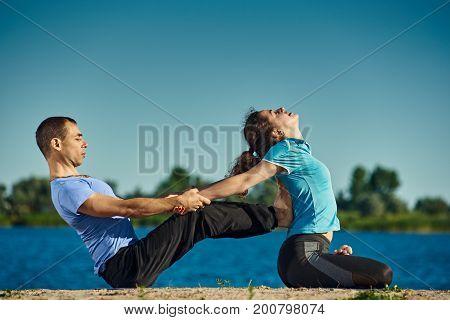Sporty athletic man and woman practicing paripurana Navasana and Padmasana