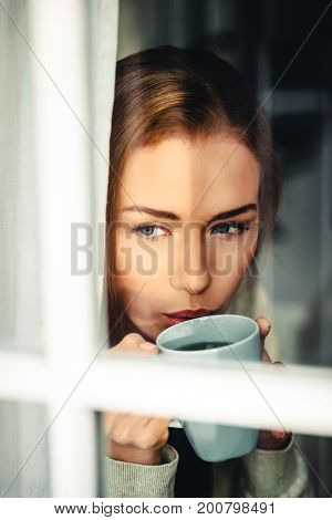 Beautiful caucasian woman drinking hot coffee or tea.