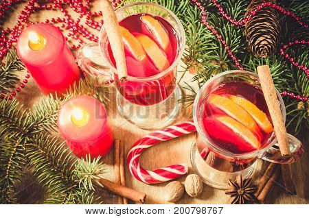 Two Glasses with Mulled Wine Red Candles Spices and Christmas Tree Branches on wooden background. Vintage Toned. Selective Focus. Top View