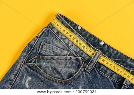 Close up of jeans belt loops and pocket. Jeans with yellow measure tape instead of belt. Healthy lifestyle and dieting concept. Top part of denim trousers isolated on yellow background.