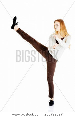 Beautiful casual woman doing a kick.