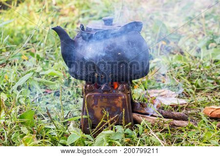 The smoked kettle is heated on the camp portable stove