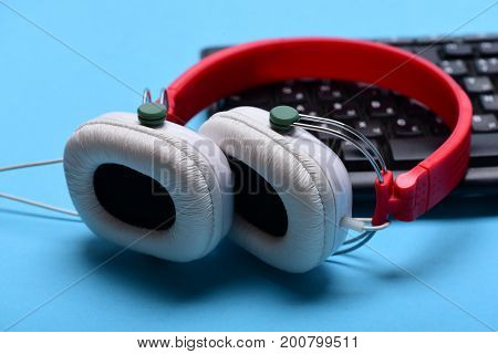 Headphones And Black Keyboard. Electronic Appliances Isolated On Cyan Background