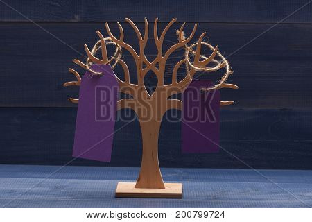 Organizer for jewellery made of wood on dark blue vintage background. Earring holder with purple price tags close up. Beauty and shopping concept. Decorative tree to store jewellery.