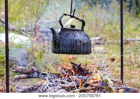 An old kettle over the camp fire. The kettle boils water for tea