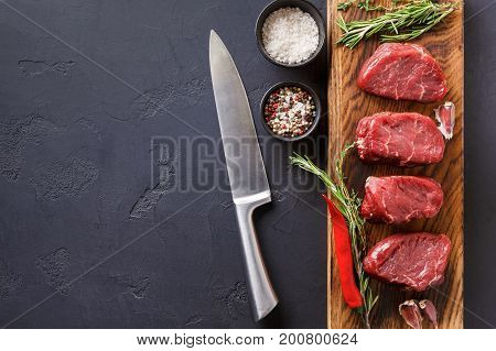 Raw filet mignon steaks with herbs and spices. Ingredients for restaurant dish. Fresh meat, salt, rosemary, garlic and chilli on wooden board, chef knife at black background with copy space, top view