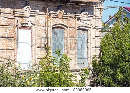 Old abandoned house made of red brick with clogged windows