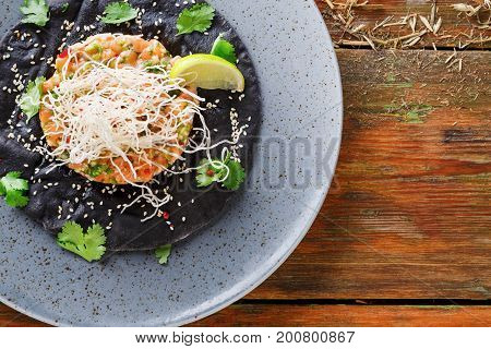 Exclusive restaurant food. Traditional hawaiian appetizer - poke with fresh salmon on black sesame flat cake on gray plate. Healthy meals in modern serving on wooden background, copy space, top view