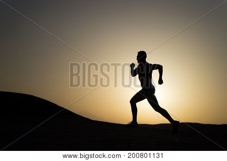speed. silhouette of running man on sunset fiery sky background in mountain sport and recreation future and success people and nature speed and healthy lifestyle