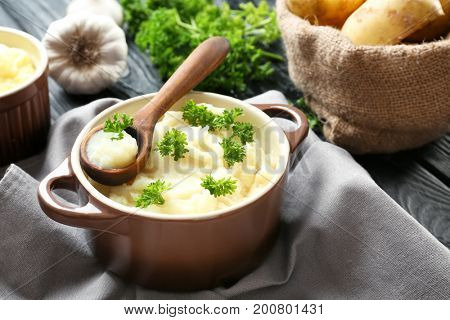 Casserole and wooden spoon with mashed potatoes on table