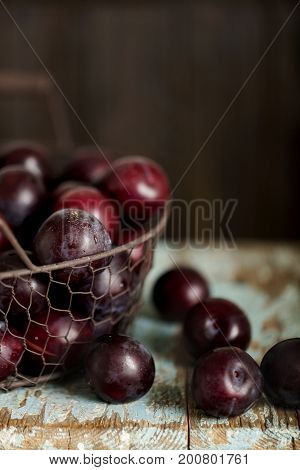 Ripe plums in a basket on a wooden background. Selective focus.