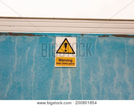 A Sign On Blue Wall Saying Warning Anti Climb Paint