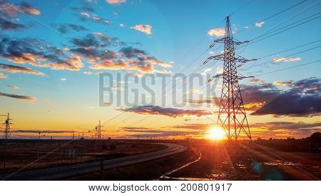 Landscape: High voltage electric tower on sunset background, road, blue sky and clouds.