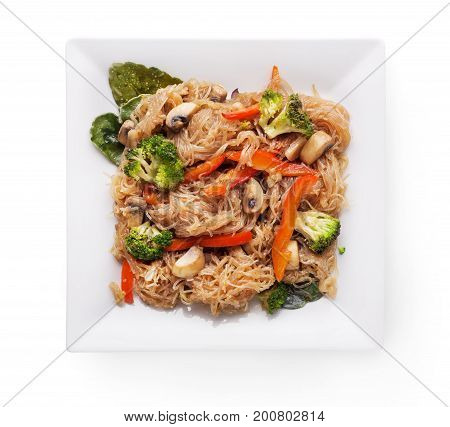 Asian food plate isolated at white background. Funchoza salad. Rice noodles with stir fry broccoli, pepper and mushrooms, top view