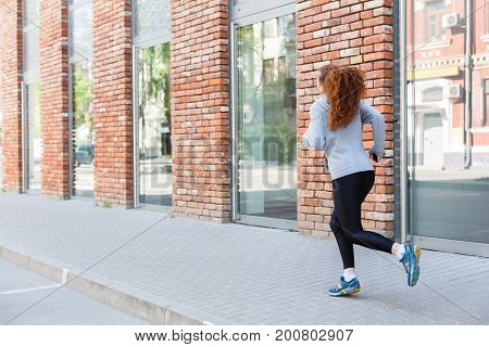 Young redhead woman running in city near brick building with mirror windows, copy space, back view