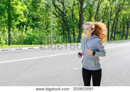 Woman listening music during morning running outdoor, copy space