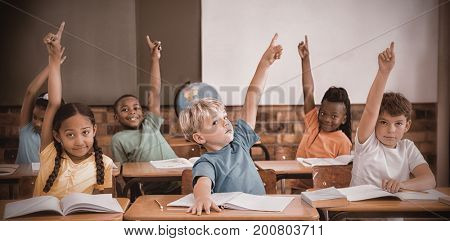 Cute pupils raising their hands at elementary school