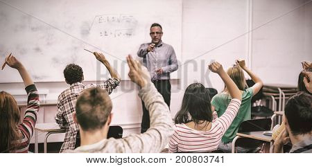 Rear view of students with hands raised with teacher in classroom