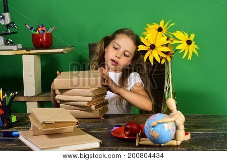 Girl Sits At Desk With Colorful Stationery, Books And Flowers