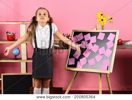 Schoolgirl With Confused Face And Gestures In Classroom