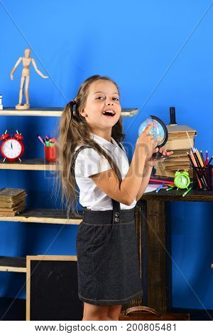 Girl Stands By School Items. Schoolgirl With Interested Face