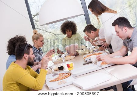 multiethnic group of happy friends spending time together with food and soda drinks, eating at home concept