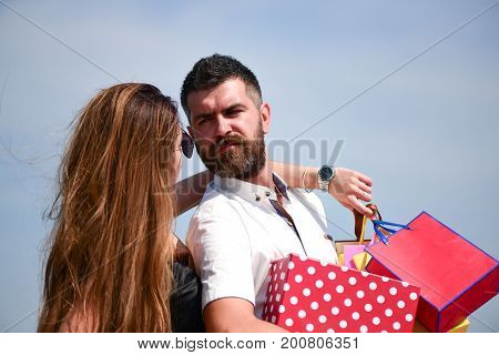 Man with beard and long haired woman hold shopping bags. Sexy girl and guy with calm faces make purchases. Couple in love carries pink packets on blue sky background. Shopping and relationship concept