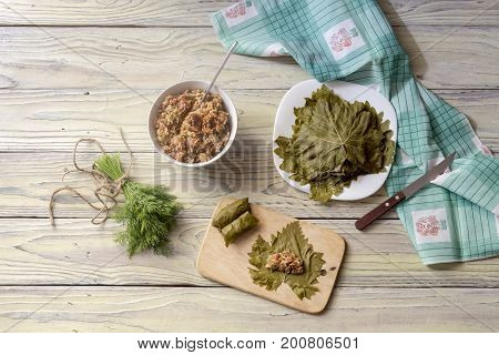 Preparation of dolmas in grape leaves on a wooden table closeup