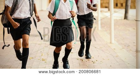 Smiling school kids running in corridor at school