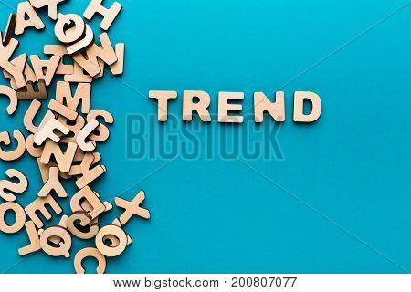 Word Trend on blue background, with pile of wooden english letters. Popular things concept