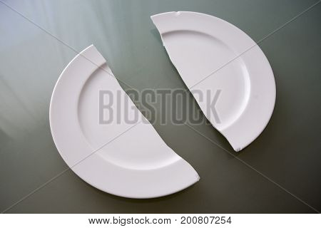 closeup of broken white plate on glass table