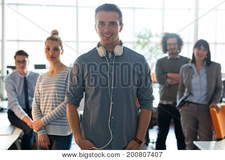 Portrait of smiling young casuall businessman with colleagues in background at the office