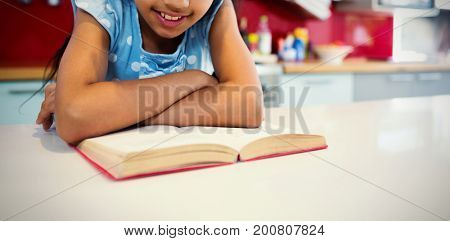 Girl reading book at kitchen counter