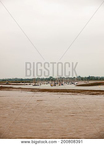 Lots Of Moored Boats In The River In The Distance Behind Mud Overcast Day Sky Empty