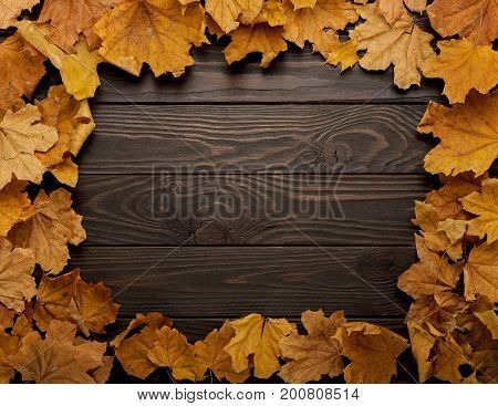 Flat lay frame of autumn leaves on a wooden background. Selective focus.