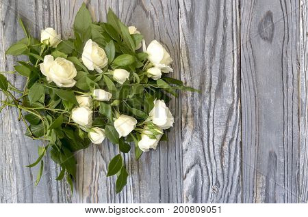 Bouquet of white roses on a wooden background