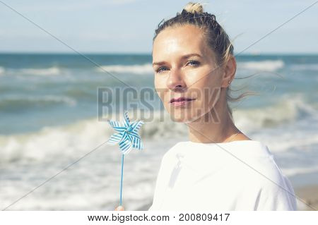 beautiful blond woman sitting on the beach with a pinwheel