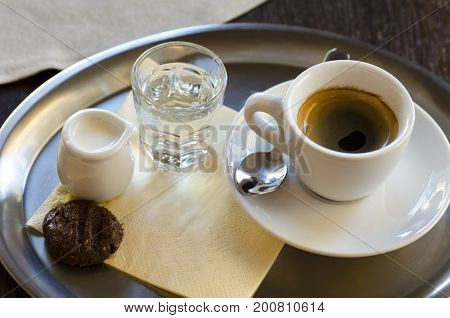 Close-up view of a cup of coffee with milk a glass of water and a cracker standing on a stainless steel tray on a paper napkin