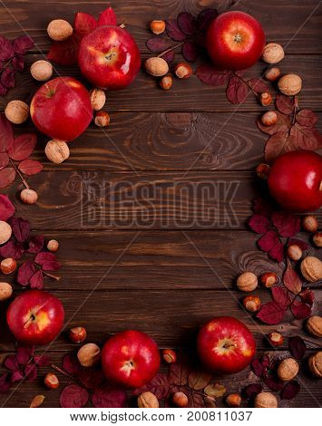 Flat lay frame of autumn crimson leaves hazelnuts walnuts and apples on a dark wooden background. Selective focus.
