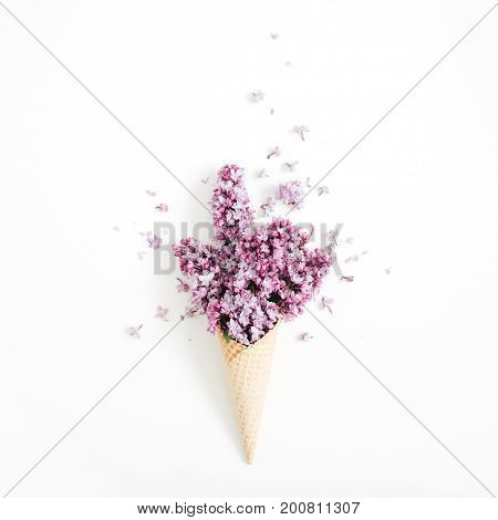 Waffle cone with lilac flower bouquet on white background. Flat lay top view floral background.