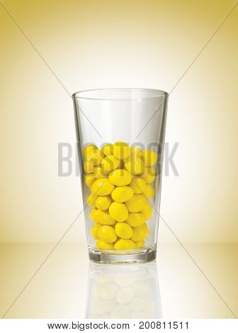 A Glass with Yellow Candy Coated Chocolate and a Yellow Background with a Hot Spot